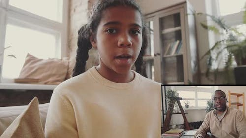 Afro-American Girl and Teacher Speaking on Video Call during Remote Lesson