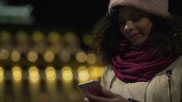 Thumbnail for Lady Watching Photos on Her Smartphone and Smiling, Nice Romantic Memories