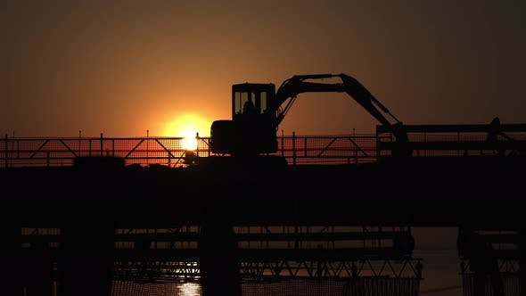 Silhouette of the Excavator on the Bridge with Passing Cars