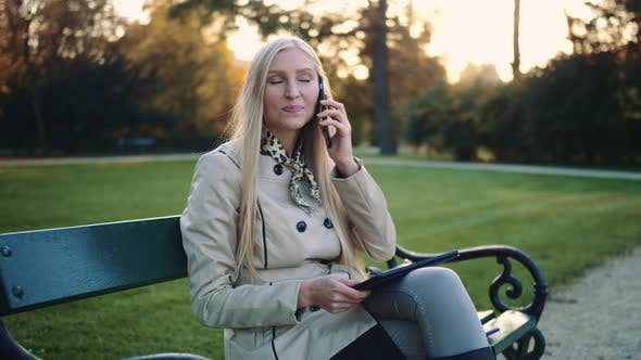 Woman with Tablet Computer and Cellphone Sitting on Park Bench