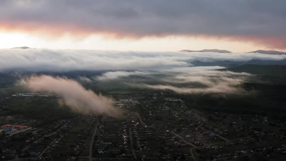 Aerial Drone Sunrise View Over Foggy Countryside with Wooden Houses