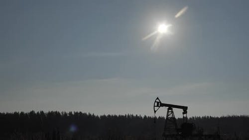 Silhouette of Old Nonworking Oil Pump From Oil Field at Sunset
