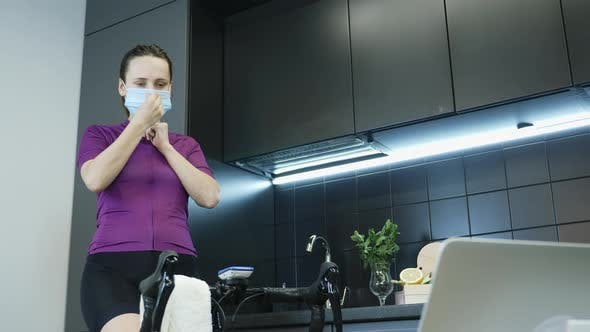 Thumbnail for Young female athlete puts on protective medical mask and preparing for indoor cycling training