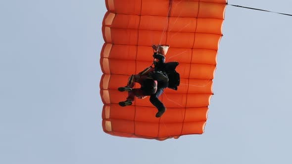 Parachutists in Tandem Flying in the Sky with a Parachute