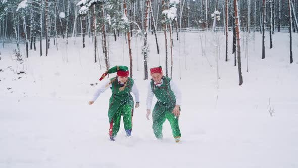 Thumbnail for Two Elves in Green Suits with Hats are Playing and Throwing Up Snow with Their Hands