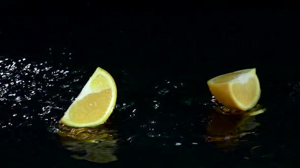 Thumbnail for Quarter of Orange Falls Into the Water. Black Background. Slow Motion