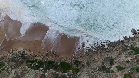 Top Down View of Huge Waves Crashing Into the Coastline