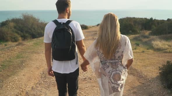 Cover Image for Young Beautiful Couple Walking on the Sand Road Near the Sea Side and Holding Hands