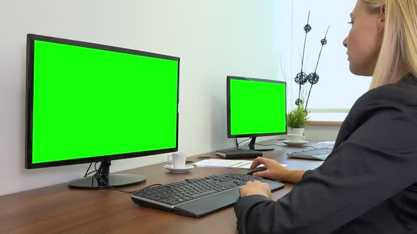 Thumbnail for An Office Worker Sits at A Desk and Works on A Computer with A Green Screen