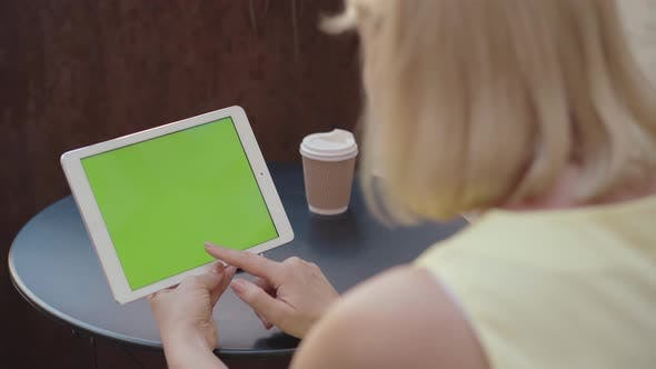 Unrecognizable Woman Holding Tablet with Chromakey Screen Outdoors and Drinking Coffee. Blond