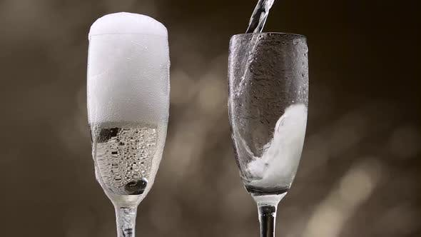 Thumbnail for Champagne Pouring in Two Glasses of Steamy Green Bottle. Bokeh Background. Close Up