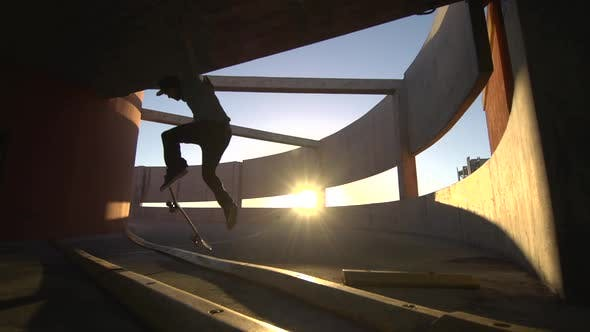 Thumbnail for Silhouette of a young man skateboarding down a spiral ramp in a parking garage at sunset.