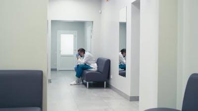 Tired Doctors Meeting in Hospital Corridor