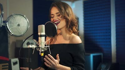 Beautiful young singer who recorded a song in a professional recording studio. Female vocal
