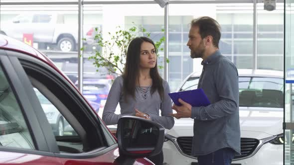 Thumbnail for Mature Salesman Talking To His Female Customer Offering Her a Car