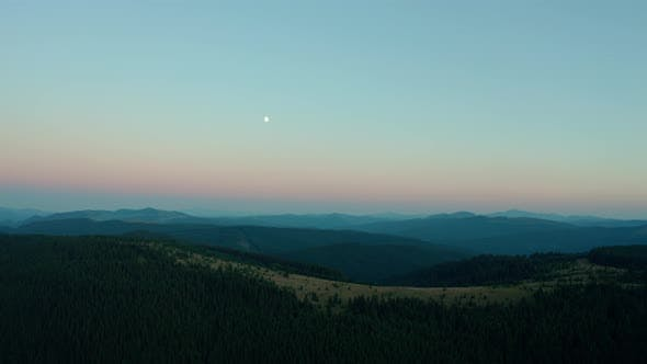 Thumbnail for Aerial Drone View a Beautiful Evening in the Mountains with the Moon. Wide Shot