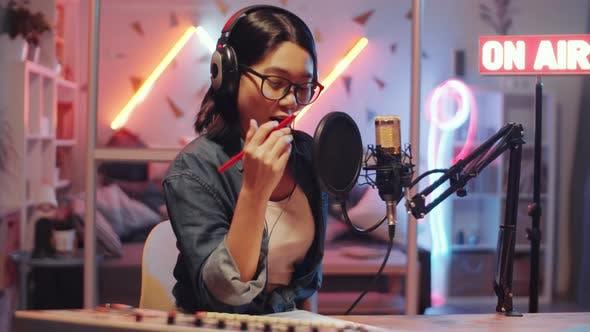 Asian Woman Recording Podcast in Home Radio Studio