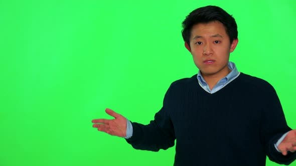 Thumbnail for A Young Asian Man Looks at the Camera and Gesticulates in Frustration - Green Screen Studio