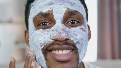 African American which Poses Into Camera while Applying Face Mask
