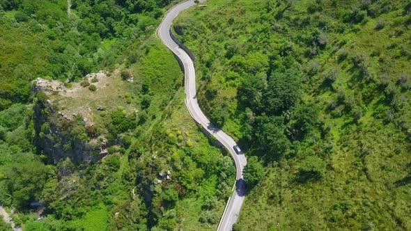 Thumbnail for Aerial Top Down Cars Driving on Winding Serpentine Road, Camera Locked Above Twisted Mountain Road