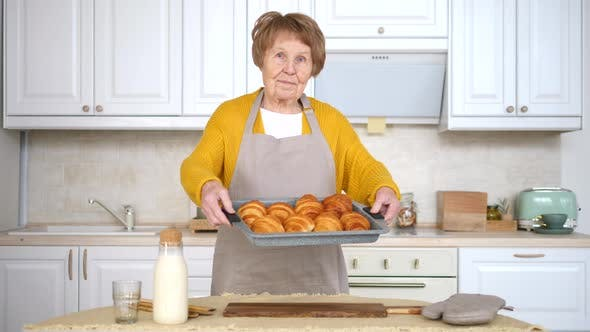 Elderly Woman Holding Baking Tray With Pastry. Granny With Baked Croissants.