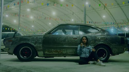 a Sad Thai Girl Sits Smoking Leaning Against a Rusty Car at Night