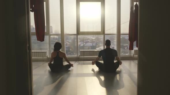 Thumbnail for Man and Woman Practice Yoga Meditation in a Spacious Class at Sunrise
