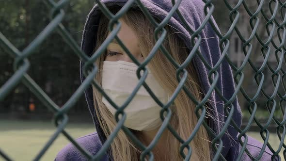 Thumbnail for Closed Border. Quarantine. Close-up of Young Woman Wearing Protective Face Mask Stand Behind Fence