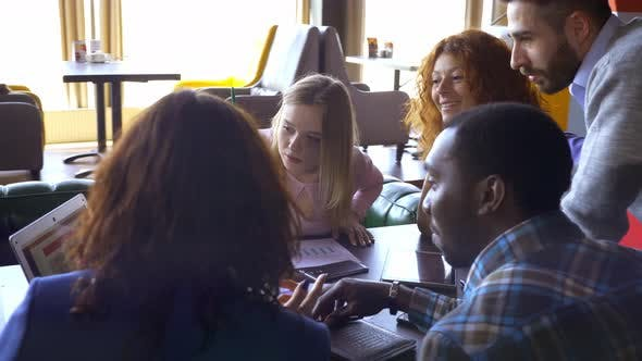 Thumbnail for Business, Startup and People Concept - Happy Creative Team with Computers and Folder Discussing