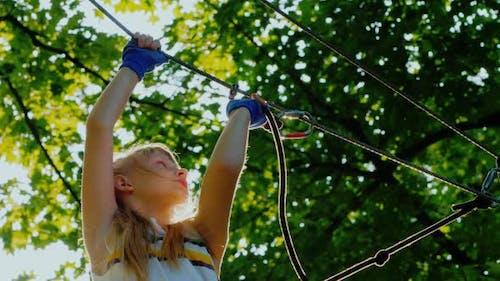 Aktives Kind klettert furchtlos die Seile zwischen den Bäumen