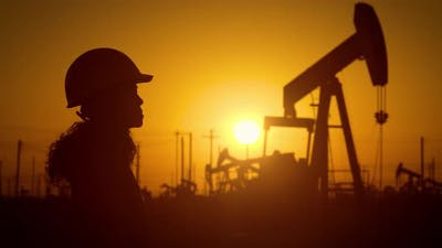 Woman engineer inspects oil pumps at sunrise
