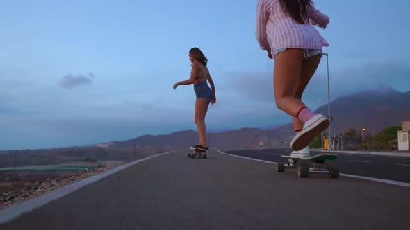 Cover Image for Close - Up of a Skateboard and Two Girls Who Are Riding on Boards From a Mountain on a Background of