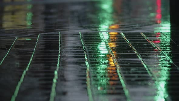 Cover Image for Evening Rain, Road Lights Reflecting on Wet Sidewalk