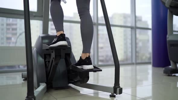 Young woman working out on stepper at gym exercising