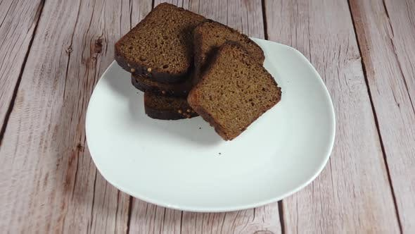 Two Slices of Rye Bread Fall on the White Plate