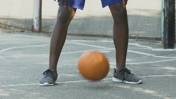 Cover Image for Sportive Black Man Making Tricks with Ball, Playing Basketball, Active Lifestyle