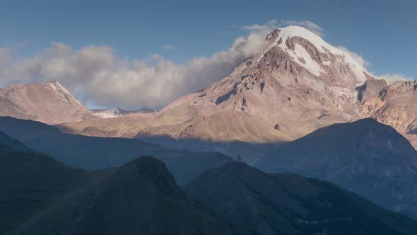 Thumbnail for Alpine Landscape View of Kazbek Mountain Covered with Snow, Gorges Ancient Church on Hill