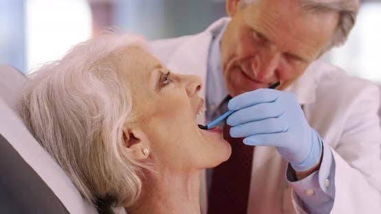 Thumbnail for Friendly senior dentist examining elderly woman's teeth