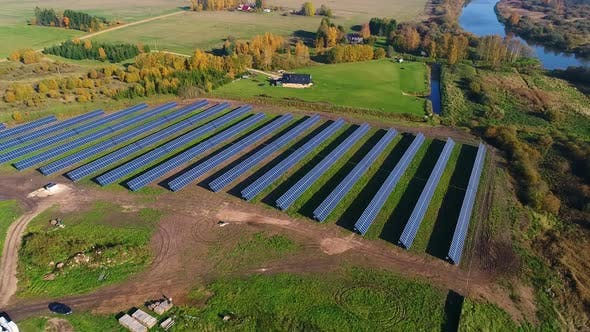 Thumbnail for Luftaufnahme von Solarpaneelreihen in der Nähe eines Waldes im Herbst, Estland.