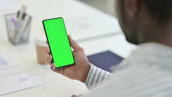 Rear View of African Man Doing Video Call on Smartphone with Chroma Screen