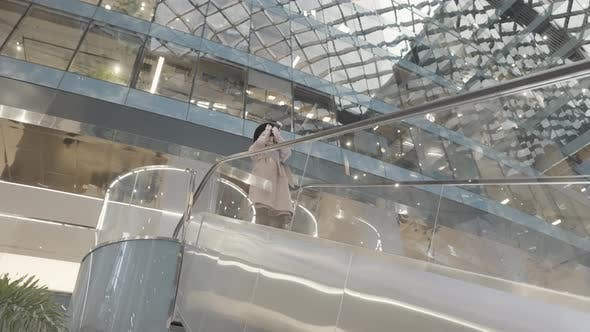 Young female taking pictures in a shopping mall