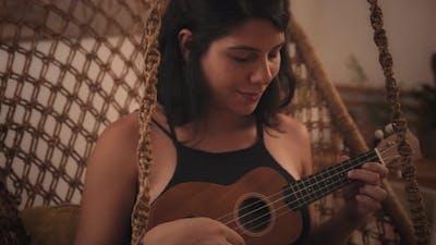 Young woman playing on ukulele guitar