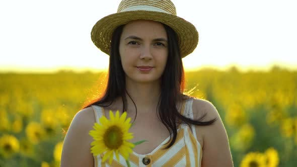Thumbnail for Beautiful Young Woman with a Hat Holds an Sunflower in Her Hands