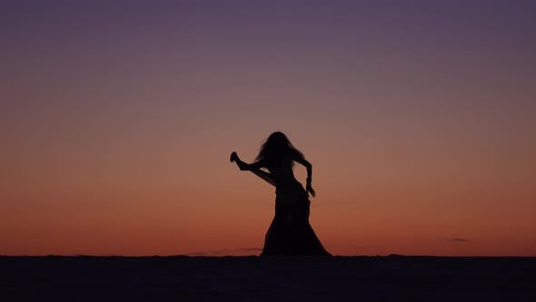 Thumbnail for Dancer Holds a Veil in Her Hands, She Dances a Belly Dance on the Beach, Silhouette