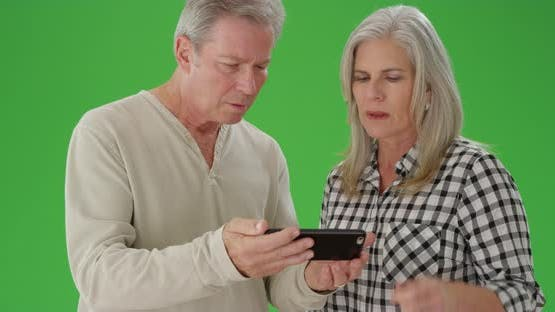 Couple of elderly caucasian people playing with a handheld device