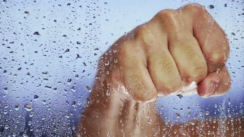 Hand Compressed Fist Hits Wet Window After Rain