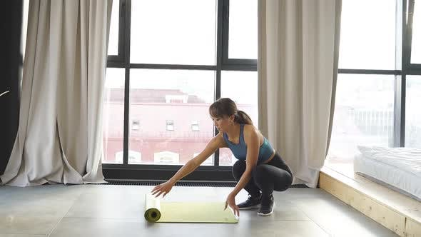 Slender Asian Woman Stretches a Fitness Mat in Her Bright Living Room a Woman Likes To Do Yoga and