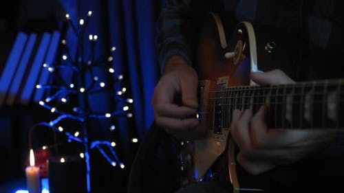 Close up of guitarist's hands are playing on electric guitar in dark room with lights