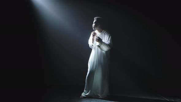 Thumbnail for A Young African American Man in a White Hoodie Looks at the Beam of Light in Dismay and Says Wow