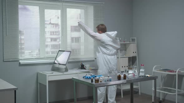 Man Put on Protective Workwear in the Laboratory